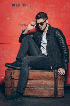 cool man: Handsome treasure. Handsome young man adjusting his sunglasses while sitting on wooden chest against red background Stock Photo