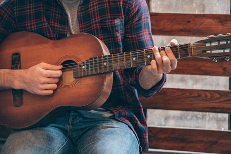 chord: Playing perfect chord. Close-up part of young man playing guitar while sitting at windowsill Stock Photo
