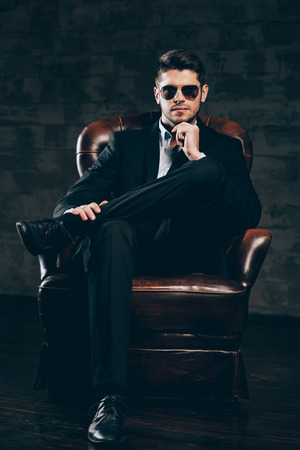 legs crossed at knee: Mr. Perfection.Young handsome man in suit and sunglasses holding hand on chin and looking at camera while sitting in leather chair against dark grey background