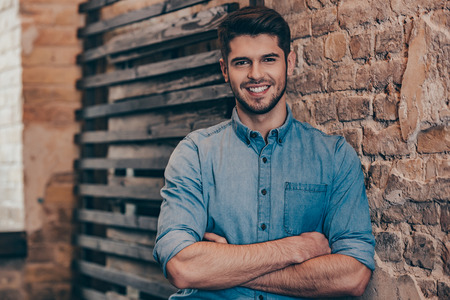 men standing: Smiling and handsome.Handsome young man keeping arms crossed and looking at camera with smile while standing against brick wall