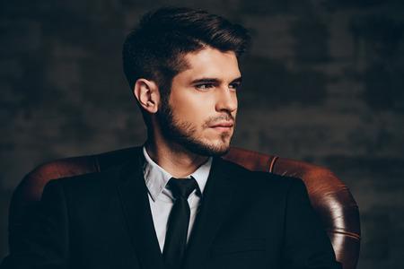 man.Portrait moderna del hombre hermoso joven en el juego que sostiene sus gafas de sol y mirando a la cámara mientras está sentado en la silla de cuero sobre fondo gris oscuro Foto de archivo
