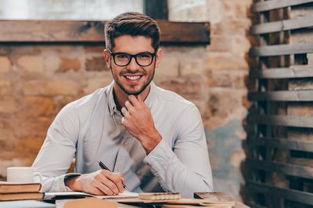 Trabalhando com prazer. Homem novo considerável nos vidros fazendo algumas anotações em seu bloco de anotações e olhando a câmera com um sorriso enquanto está sentado em seu lugar de trabalho