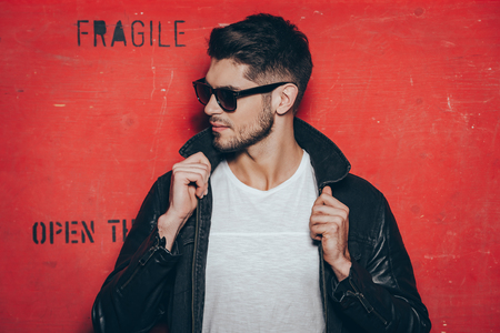 one adult only: Gorgeous and handsome. Handsome young man in sunglasses adjusting his jacket and looking away while standing against red background