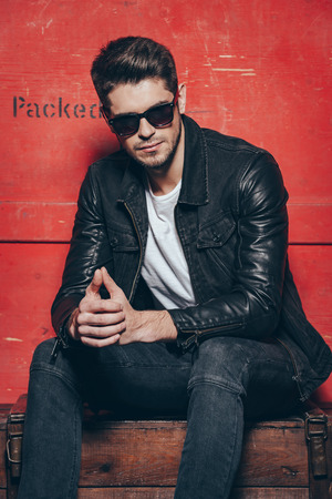 masculinity: Style and masculinity. Handsome young man in sunglasses keeping hands clasped while sitting on wooden chest against red background