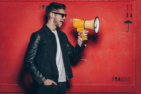 only one person: Fashion announcement. Side view of handsome young man in sunglasses holding megaphone and keeping mouth open while standing against red background