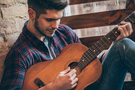 windowsill: Perfect chord. Close-up of handsome young man playing guitar while sitting at windowsill