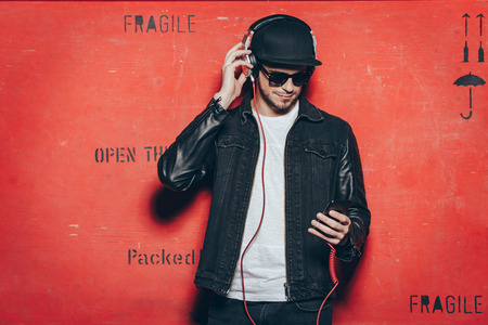 male fashion model: Style and music. Handsome young man adjusting his headphones and looking at his smart phone while standing against red background