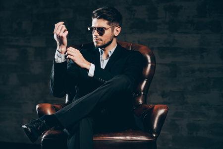 Everything must be perfect.Young handsome man in suit and sunglasses adjusting sleeve on his shirt while sitting in leather chair against dark grey background
