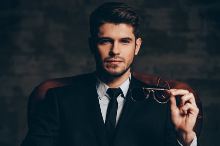 소송에서 젊은 잘 생긴 남자의 숨막히는 look.Portrait 어두운 회색 배경에 가죽의 자에 앉아있는 동안 자신의 선글라스를 잡고 카메라를 찾고