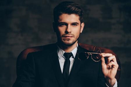 look.Portrait mozzafiato di giovane uomo bello in vestito che tiene gli occhiali da sole e guardando la fotocamera, mentre seduto in poltrona in pelle su sfondo grigio scuro Archivio Fotografico