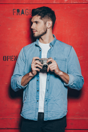 old fashioned: Handsome photographer. Handsome young man in sunglasses keeping arms crossed and looking at camera while standing against red background