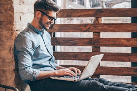 Blogger no trabalho. Opinião lateral do homem novo considerável que trabalha no portátil e que sorri ao sentar-se no windowsill
