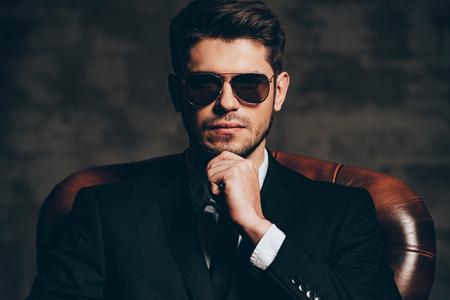 Elegante y perfect.Portrait de joven guapo en traje de la mano en la barbilla y mirando a la cámara mientras está sentado en la silla de cuero sobre fondo gris oscuro