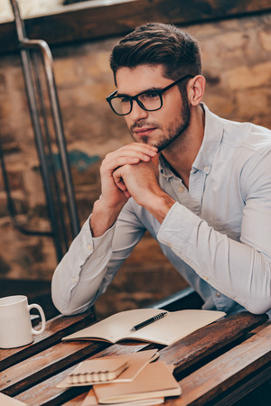 hands clasped: Thinking about solution. Handsome thoughtful young man keeping hands clasped and looking away while sitting at his working place