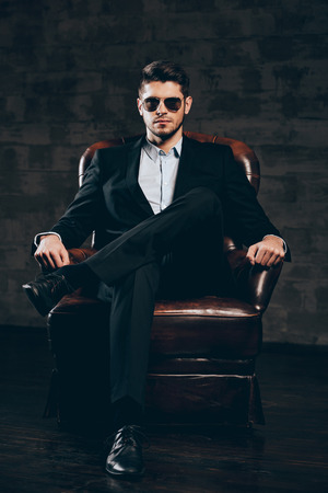 Elegance and masculinity.Young handsome man in suit and sunglasses holding hand on chin and looking at camera while sitting in leather chair against dark grey background