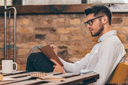 Wijzend op zijn ideeën. Zijaanzicht van knappe jonge man in glazen schrijven in zijn notitieblok tijdens de vergadering op zijn werkplek Stockfoto
