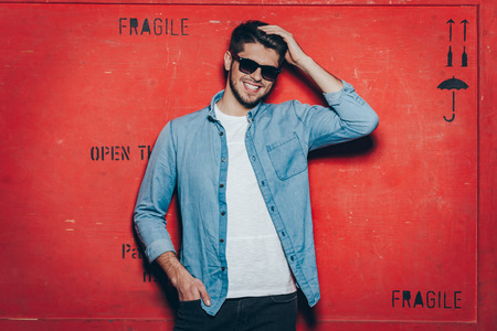 Cheerful and trendy.Handsome young cheerful man in sunglasses keeping hand in hair and looking at camera with smile while standing against red background