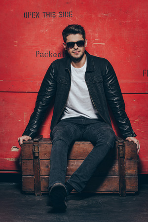 man shirt: Modern and handsome. Handsome young man adjusting his sunglasses while sitting on wooden chest against red background