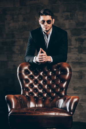 man in chair: Charming and elegant. Young handsome man in suit and sunglasses leaning on leather chair and looking at camera while standing against dark grey background
