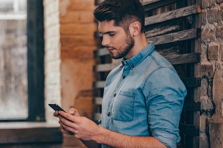 hombres jovenes: Mensaje a la vista de her.Side reflexivo joven hermoso que sostiene teléfono inteligente y mirándolo mientras se inclina la pared de ladrillo en el interior de loft