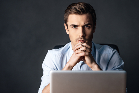 handsome young man: Concentration and elegance. Confident handsome young man looking at camera and keeping handsclasped while sitting with laptop against black background Stock Photo
