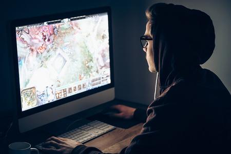 jugando videojuegos: juego de la noche. Vista lateral del hombre joven que juega al juego video mientras se está sentado en la mesa en una habitación oscura Foto de archivo