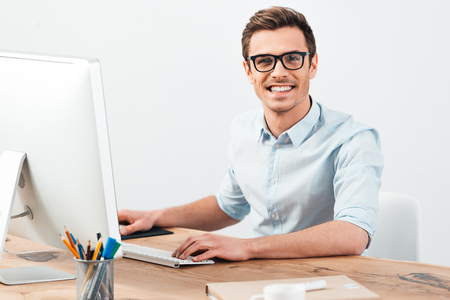 Best manager. Cheerful young handsome man in glasses working on computer and looking at camera with smile while sitting at his working place
