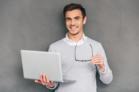 man with laptop: Ready to help you. Confident young man looking at camera with smile and holding laptop while standing against grey background Stock Photo