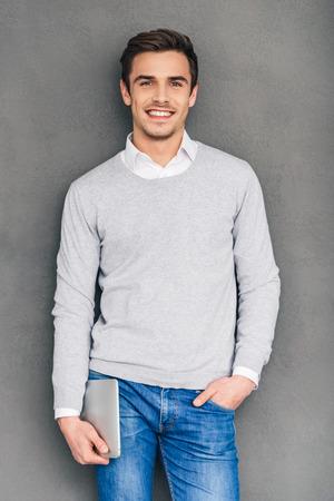 hombres jovenes: El Sr. Experto. Seguro de joven mirando la c�mara con sonrisa y llevar la tableta digital mientras est� de pie contra el fondo gris Foto de archivo
