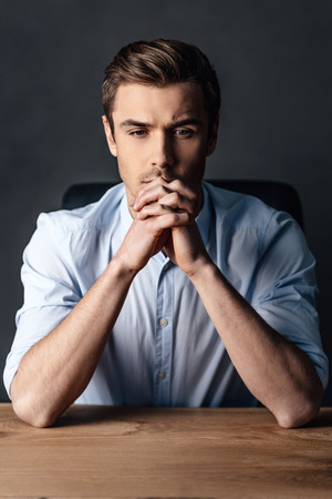 hands clasped: Searching for the right solution. Handsome young man keeping hands clasped and looking thoughtful while sitting against black background
