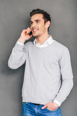 one people: Nice to hear your voice! Confident cheerful young man talking on mobile phone and keeping hand in pocket while standing against grey background