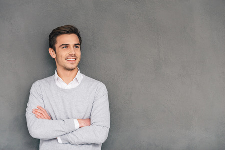 business person: Looking in future with smile. Confident young man keeping arms crossed and looking away with smile while standing against grey background