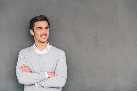 Suchen Sie in Zukunft mit einem Lächeln. Überzeugter junger Mann mit einem Lächeln die Arme verschränkt und schaut weg zu halten, während die grauen Hintergrund gegen