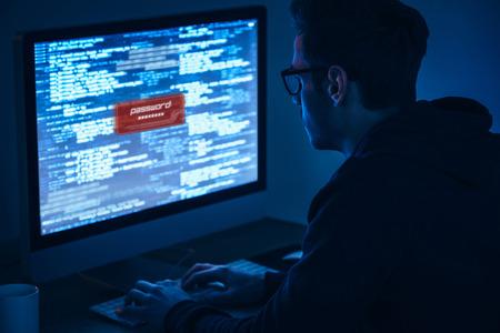 コンピューターのセキュリティ。若い男を入力して、暗い部屋でテーブルに座ってコンピューターのモニターを見ての背面図