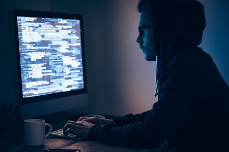 dark side: Computer spy. Side view of young man typing and looking at computer monitor while sitting at the table in dark room Stock Photo