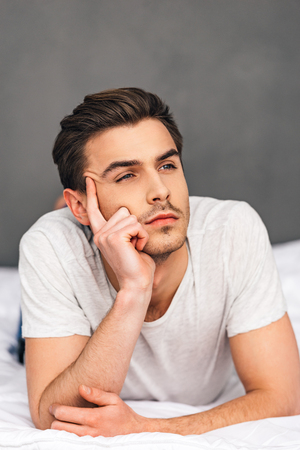 pensive man: Day dreaming. Pensive young man looking away and dreaming about something while lying on front in bed against grey background
