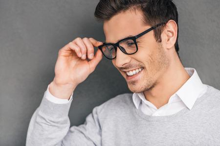 hombres jovenes: La elegancia y el éxito. Vista lateral de un joven confía en el ajuste de sus gafas y mirando a otro lado con una sonrisa mientras está de pie contra el fondo gris Foto de archivo