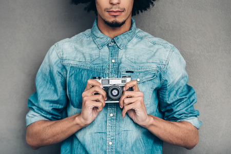 retro styled: Retro click.Close-up part of young African man in jeans shirt holding retro styled camera while standing against grey background Stock Photo