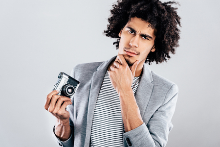 retro styled: Do you want a photo or not? Handsome young African man holding retro styled camera and looking at camera while standing against grey background