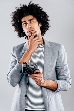 retro styled: What shall I shoot next? Handsome young African man holding retro styled camera and looking thoughtful while standing against grey background Stock Photo