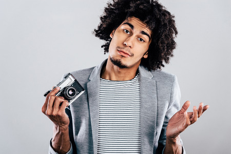 retro styled: Out of camera film. Handsome young African man holding retro styled camera and looking confused while standing against grey background Stock Photo