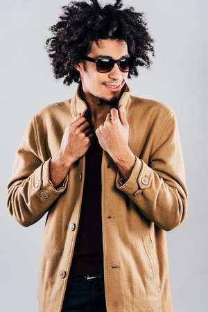 fashion clothing: Feeling cozy in his new coat. Close-up of confident young African man in sunglasses looking away with smile and adjusting his coat while standing against grey background
