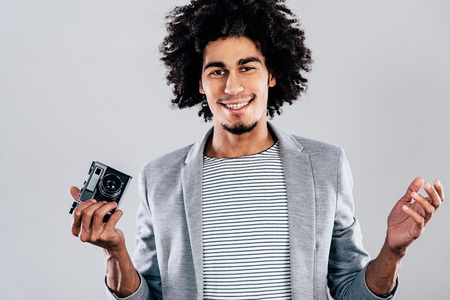 retro styled: Want a picture? Handsome young African man holding retro styled camera and looking at camera with smile while standing against grey background Stock Photo