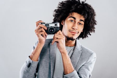 retro styled: Show me you best smile! Handsome young African man holding retro styled camera and looking at camera while standing against grey background