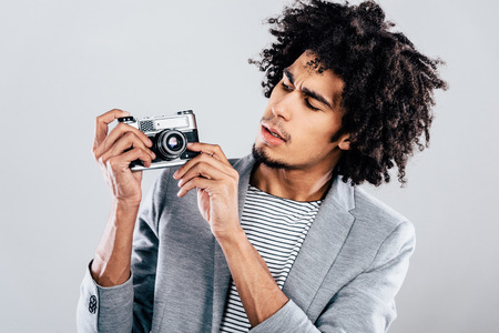 retro styled: Can this thing make selfie? Handsome young African man holding retro styled camera and looking at it while standing against grey background