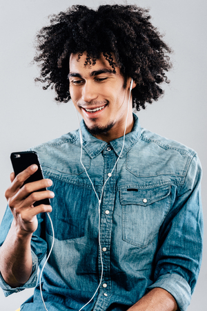 hair man: His favorite song. Cheerful young African man wearing headphones and using his smartphone with smile while sitting against grey background