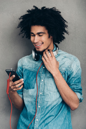 hair man: That is really great playlist. Young African man wearing headphones and using his smartphone with smile while standing against grey background
