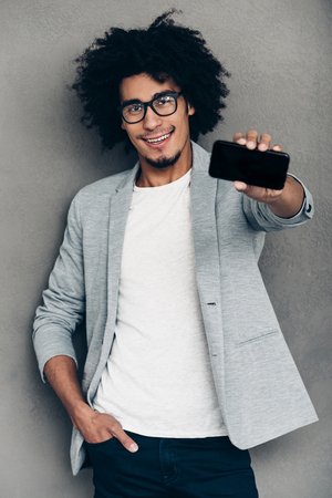 african man: Have you seen my new smart phone?Cheerful young African man showing his smart phone and smiling while standing against grey background Stock Photo