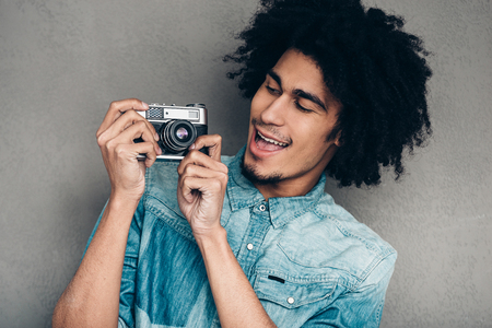 retro styled: This thing works perfectly! Handsome young African man holding retro styled camera and looking at it with smile while standing against grey background