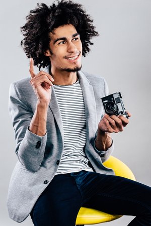 looking away from camera: Got an idea for next shoot! Handsome young African man holding retro styled camera and looking away with smile while sitting against grey background
